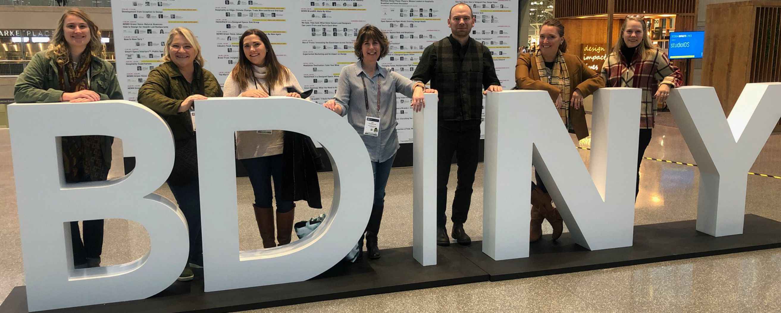rlps interiors staff behind the BD|NY sign